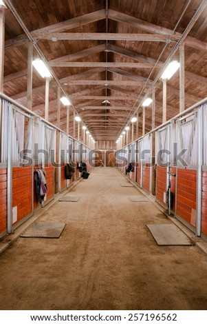 The center path through a horse barn light at the end of the tunnel - stock photo