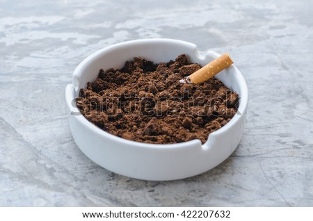 The ceramic ashtray contain coffee ground on concrete floor for protection fire from cigarette. - stock photo