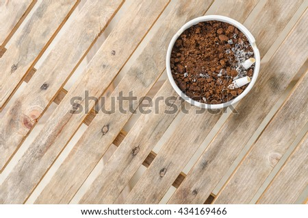 The ceramic ashtray contain coffee ground on wood table for protection fire from cigarette. - stock photo