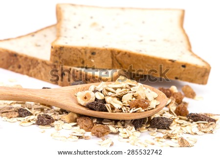 the cereal and black sesame bread with whole grain cereal flakes which mixed warming cinnamon , red skin apple , golden raisins and roasted hazelnuts on white background - stock photo