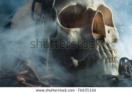 The chains of eternity locking up tormented skull of a human - stock photo