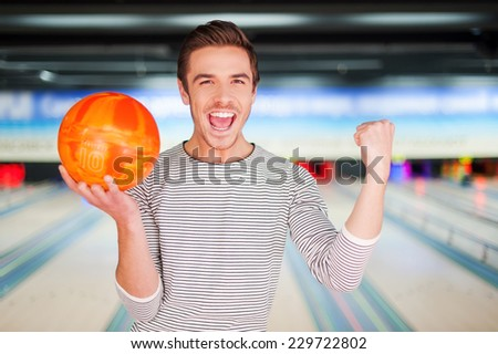 The champion of bowling. Cheerful young man holding a bowling ball and keeping arms raised while standing against bowling alleys
