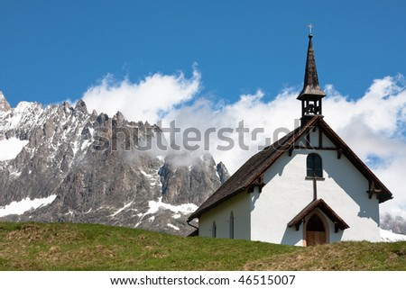 The chapel near Belalp (Switzerland) against the mountains and a blue sky - stock photo