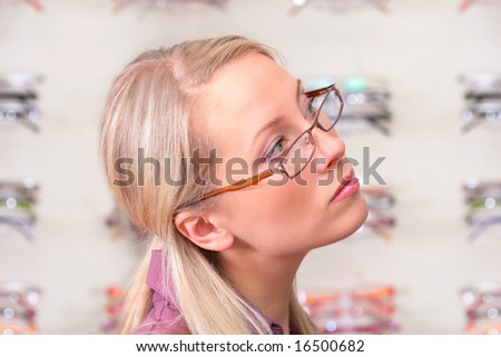 the charming blonde chooses the model of collets to glasses - stock photo