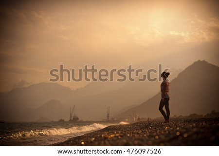 The charming girl stands near sea