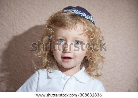 The charming little boy with blue eyes and long blond curls in Jewish knitted skullcap. Autumn holiday of Sukkot - stock photo