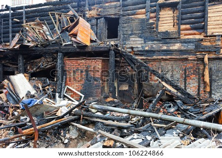 The charred ruins and remains of a burned down house. - stock photo
