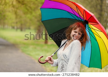 the cheerful and happy girl under a bright umbrella i springtime - stock photo