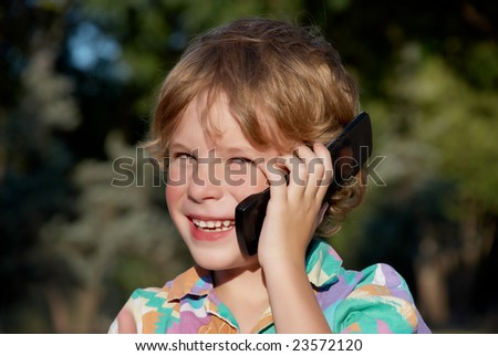 The cheerful boy with a mobile phone in park - stock photo