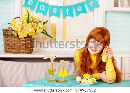 The cheerful girl with red hair in casual clothes and an apron sitting on a wooden table next to Easter decor. The decor consists of: Easter eggs, Easter bunnies, a bouquet of yellow flowers.