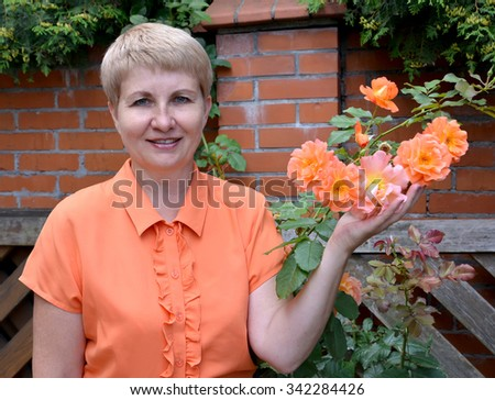 The cheerful woman of average years shows a rose hand in a garden - stock photo