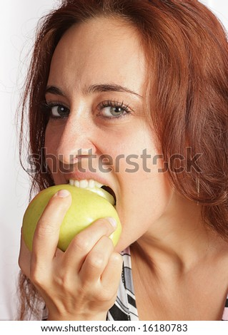 "The cheerful young girl is eating a fresh green apple, knowing the saying ""Two apples a day, keep doctor away!""."