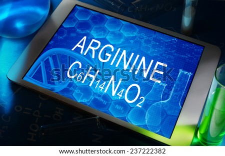 the chemical formula of arginine on a tablet with test tubes   - stock photo