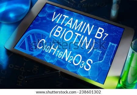 the chemical formula of Biotin Vitamin B7 on a tablet with test tubes   - stock photo