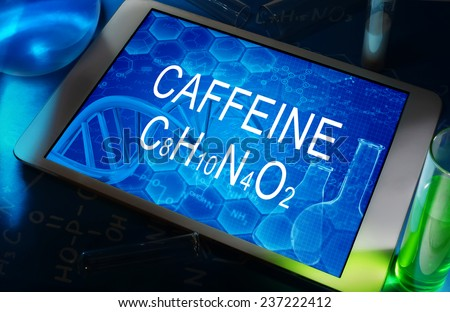 the chemical formula of caffeine on a tablet with test tubes   - stock photo