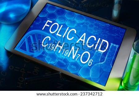 the chemical formula of Folic acid on a tablet with test tubes   - stock photo