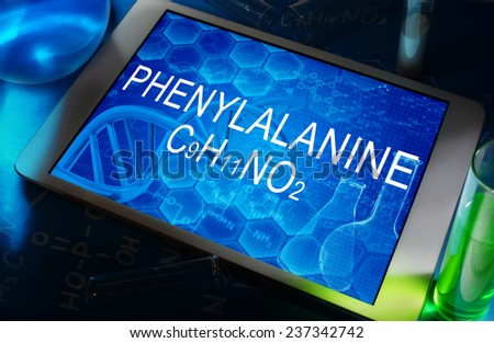the chemical formula of Phenylalanine on a tablet with test tubes   - stock photo