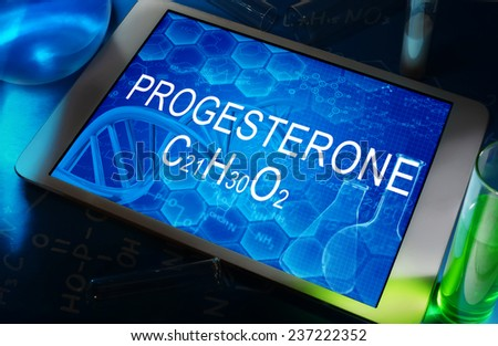 the chemical formula of progesterone on a tablet with test tubes   - stock photo