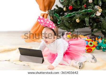 The child, a little girl looks at the plate near the Christmas tree - stock photo