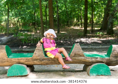 The child, a little girl sitting on a bench in the woods, summer outdoor recreation, a halt in the shade of trees, carefree childhood - stock photo