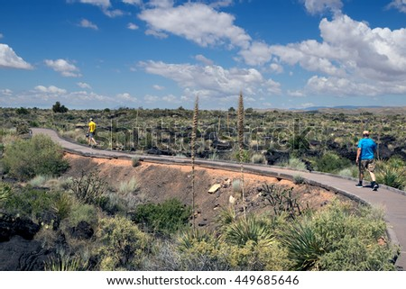 The child and his father are on the track among the solidified lava fields.  Valley of  Fires Recreation Area,  Carrizozo, New Mexico - stock photo