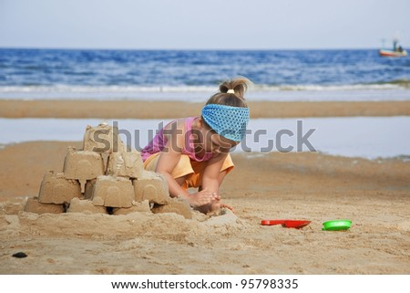 The child builds a sand castle on the beach toy shovel - stock photo