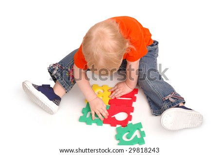 The child collects puzzles with numerals - stock photo