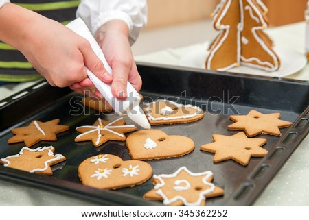 the child decorates homemade Christmas cookies - stock photo