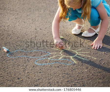 The child drawing a chalk on asphalt - stock photo