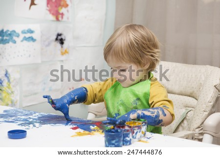 the child draws finger-type paints - stock photo