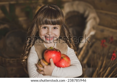 The child holds a heap of apples. - stock photo
