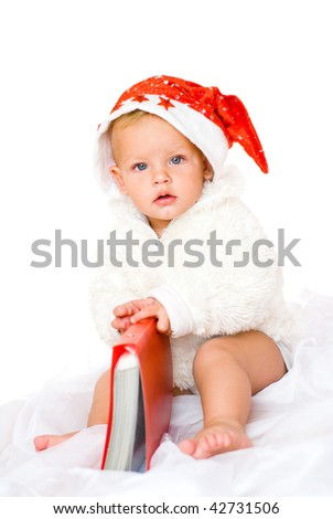 The child in a celebratory Christmas cap and in the white fur coat, isolated on a white background