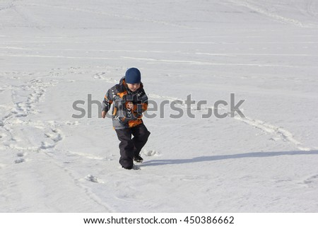 The child in a color jacket running on snow in the winter - stock photo