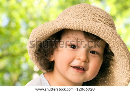 The child in a; straw-hat. - stock photo