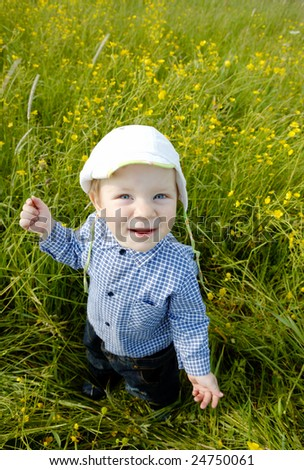 The child in the middle of a field of yellow flowers - stock photo