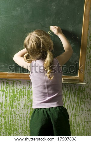 The child is in a school room.  She is doing something on the chalkboard.  Vertically framed shot. - stock photo