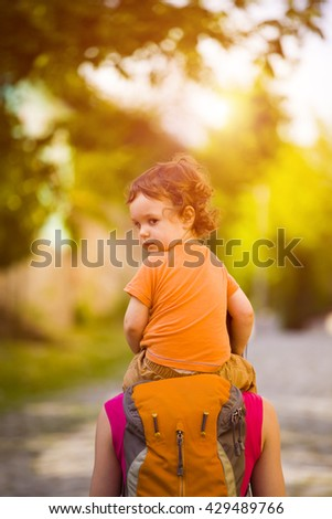 The child is sitting on mum's shoulders while traveling. - stock photo