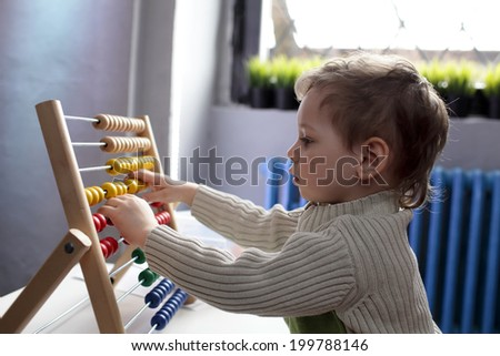 The child playing with abacus at home - stock photo