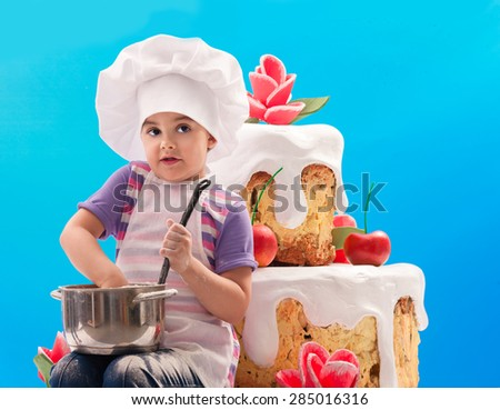 The child prepares a cream on a background of a large cake - stock photo