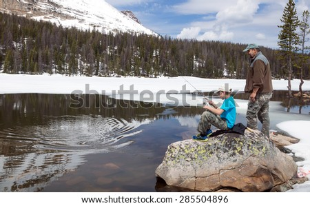 The child pulls a fish from alpine lakes.  Father ready to help.  Mirror Lake,  Uinta-Wasatch-Cache National Forest, Utah - stock photo