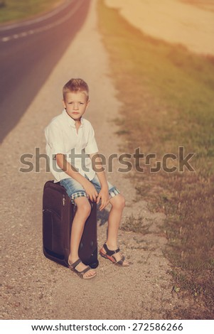 the child sits on a suitcase in the summer sunny day, the traveler, toned image - stock photo