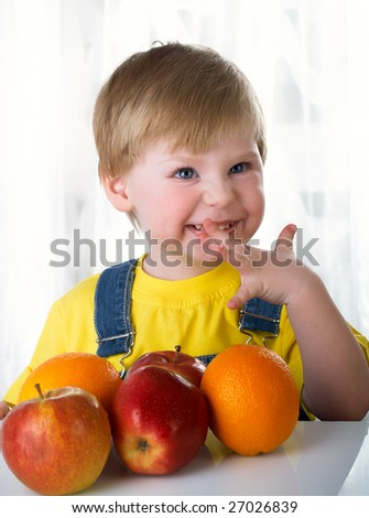 The child sits on a table with fruit