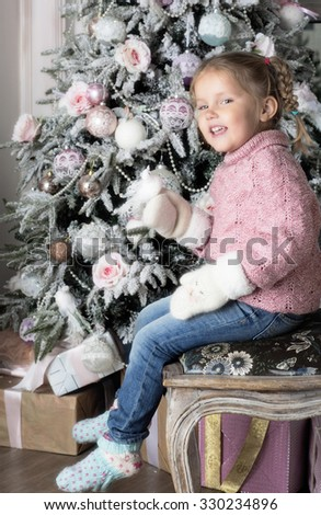 The child  sits on chair near Christmas tree.