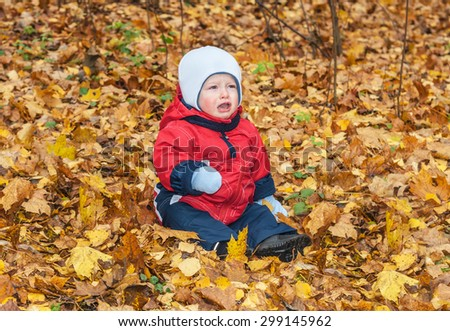 The child sits on yellow leaves and cries - stock photo