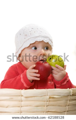 The child sits with apples in the basket. - stock photo