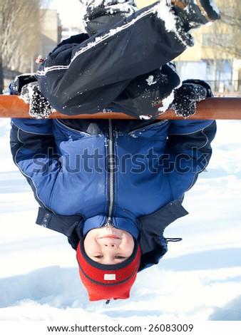 The child the boy plays in the winter in the street - stock photo