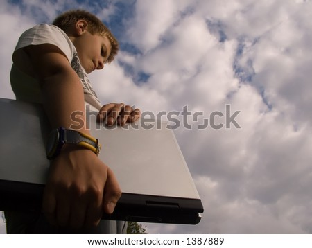 The child with a portable computer in the blue sky. - stock photo