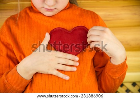 The child with a red heart in hands - stock photo