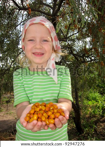 The child with sea-buckthorn berries in hands - stock photo