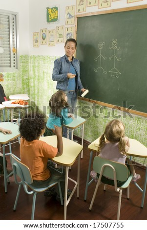 The children are in a school room.  The teacher is showing the classroom something.  Vertically framed shot. - stock photo